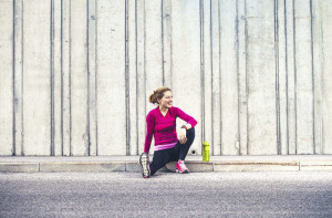 Happy young woman sitting on the sidewalk after running