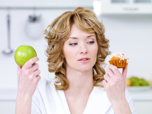 Woman is holding a muffin in her left hand and an appel in the other hand.