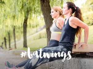 Two young women are doing dips on a parkbench.