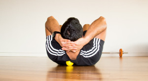 Man using a ball to massage his back.
