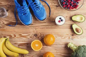 Picture detail of running-shoes and fruits set on a wooden floor.