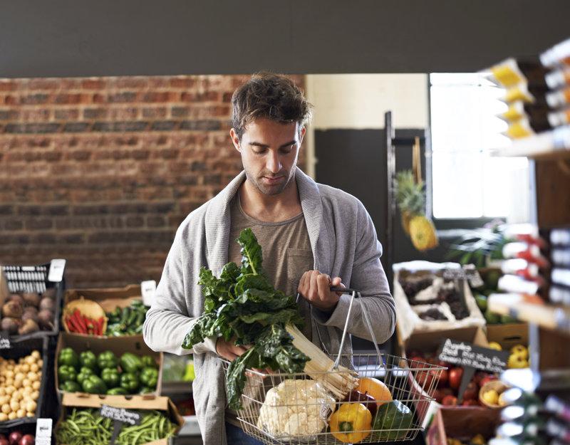 Photo d'un jeune homme dans un magazin avec un panier rempli de légumes frais
