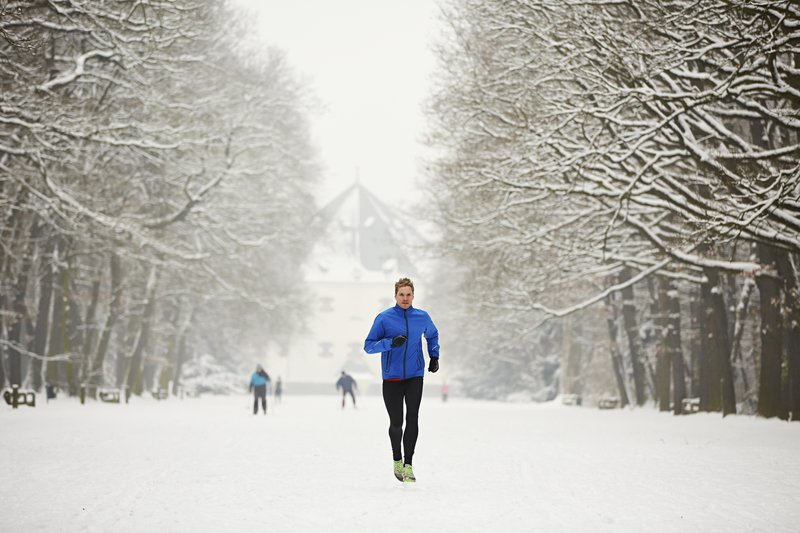 Junge Mann lauft im Schnee im Park.