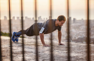 Male runner doing push ups.