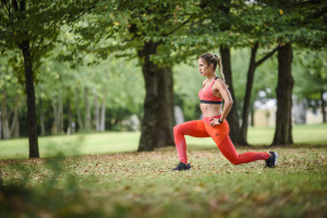 Woman is doing forward lunges in the park.
