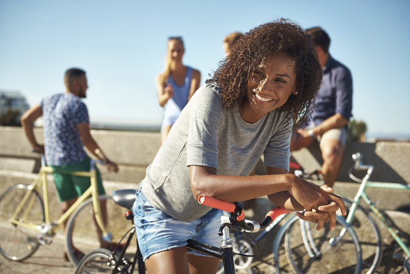 A young woman smiling happily while sitting outdoors on her bike