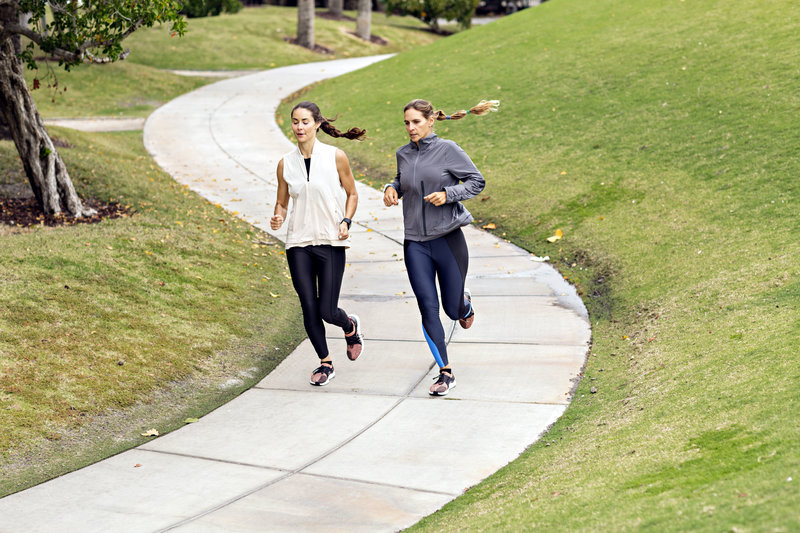Two friends running outside.