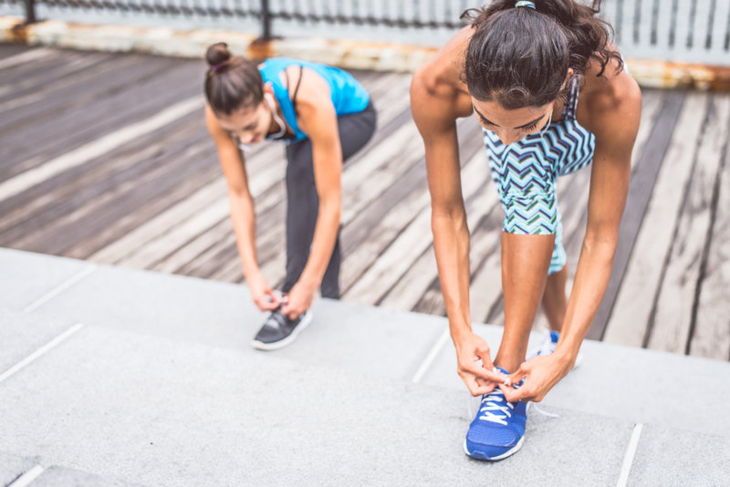 Two sportive women tying shoelaces - Girls starting a workout session outdoors, copy-space on the left