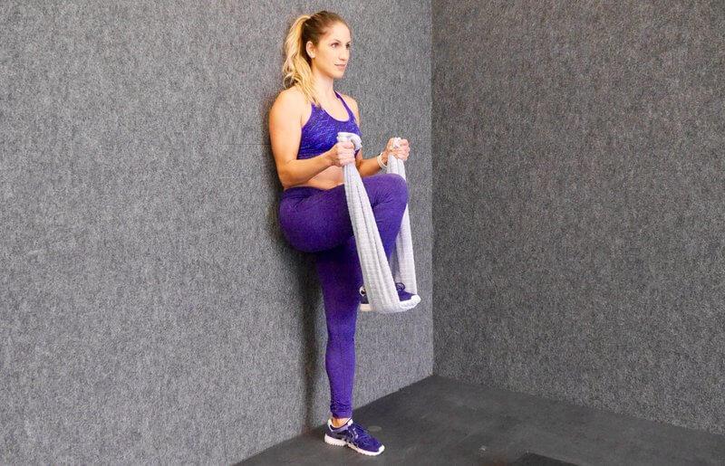 Athletic woman doing Towel biceps curls.