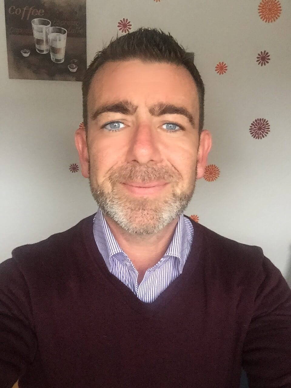 Mann mit Bart und blauen Augen.