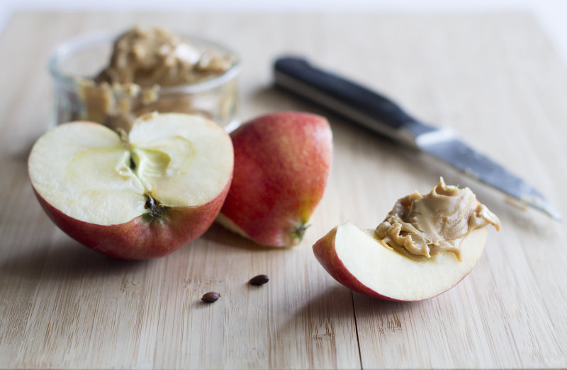 a crisp slice of apple and a scoop of creamy peanut butter, ready to be devoured!