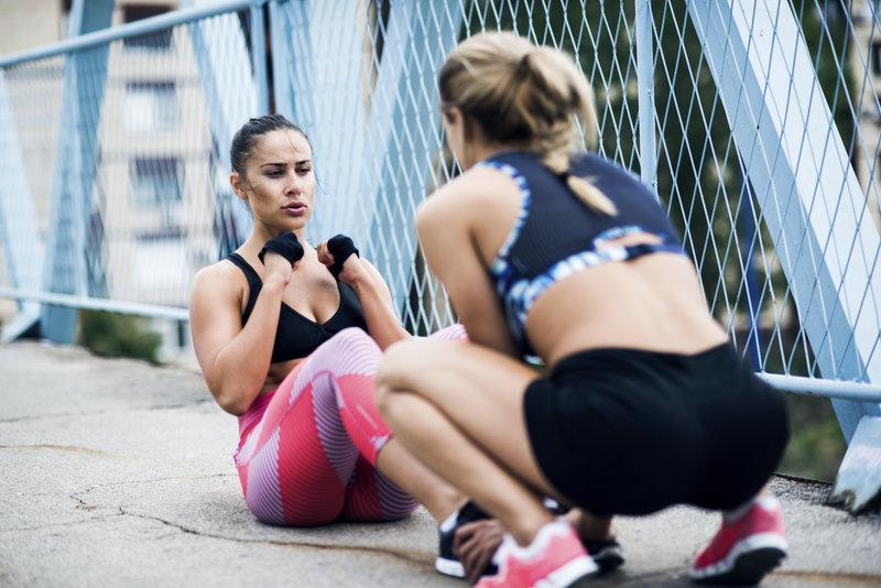 Zwei Frauen machen zusammen Bodyweight-Übungen.
