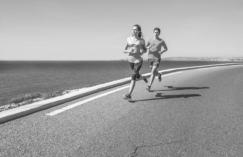 Woman and man running next to the sea