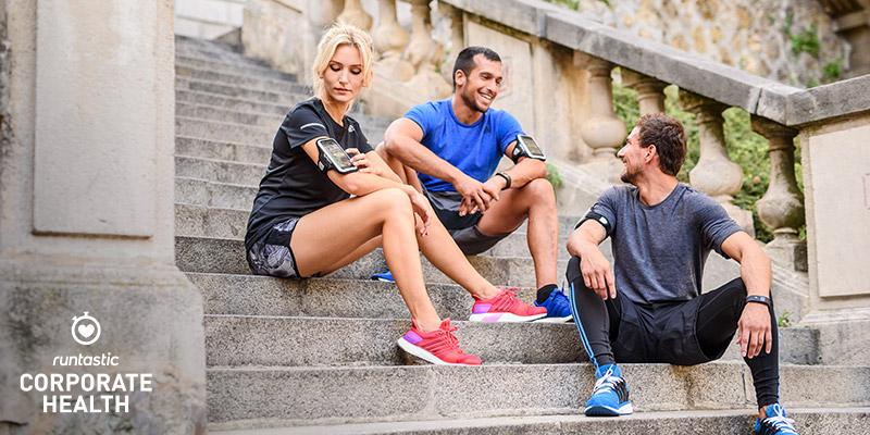 Group of friend sitting outside on stairs after their running session.
