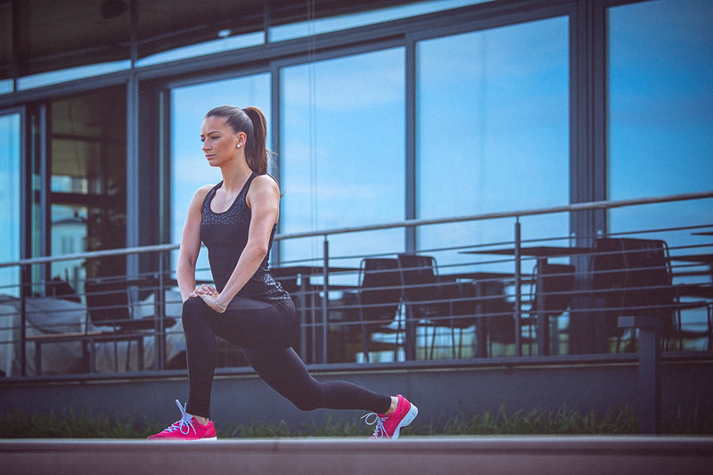 Unrecognisable female athlete, stretches her body after running. copy space has been left.