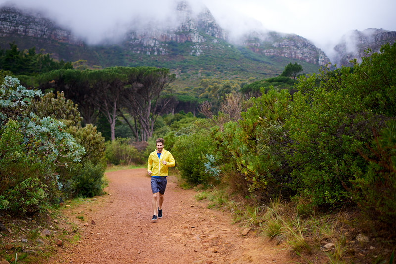 Shot of a young man running down a trail on an overcast day.