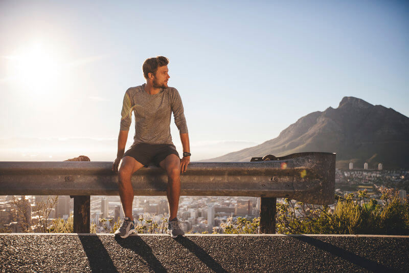 Young man is sitting on the side of the road after his morning run.