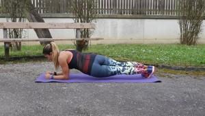Woman doing low plank twists.