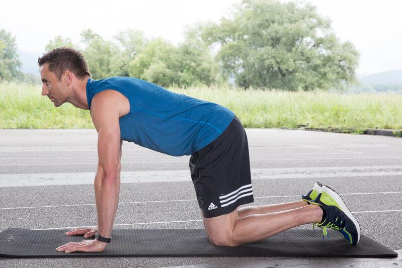 Athletic man makes a Quadrupted Limb Raise.