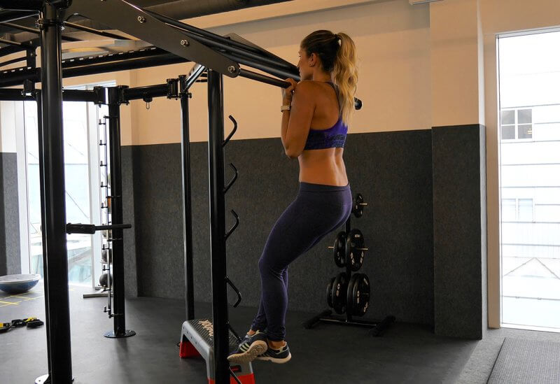 Athletic woman doing isometric Chin-ups.