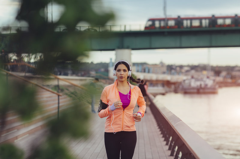 Young woman jogging in the city. She is jogging by the river and wearing headphones. Cityscape in background.