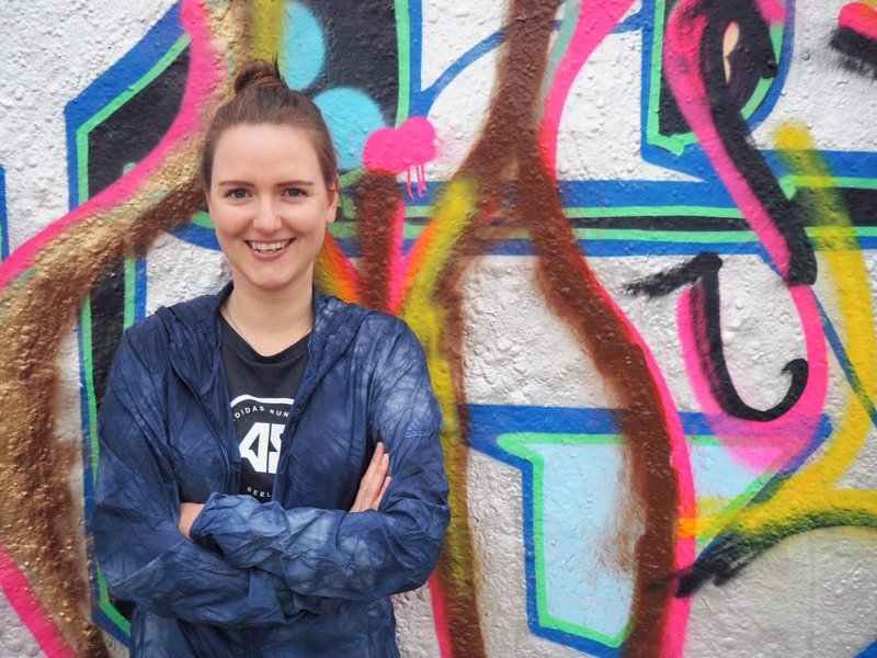 Young woman in sports clothes standing in front of a graffiti wall