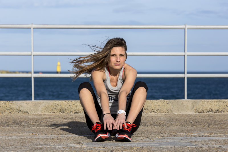 Young woman doing sit-ups near the sea