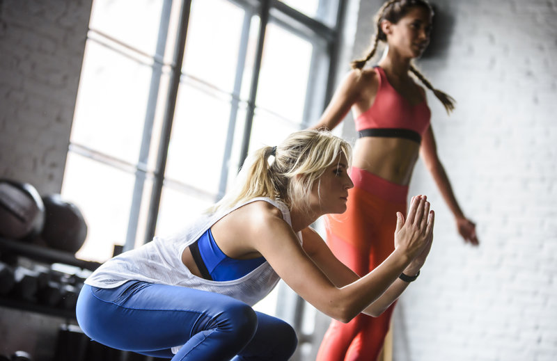 Two women are working out together indoors