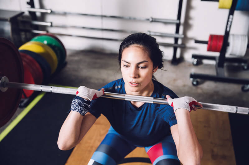 Woman is doing front squats with a barbell