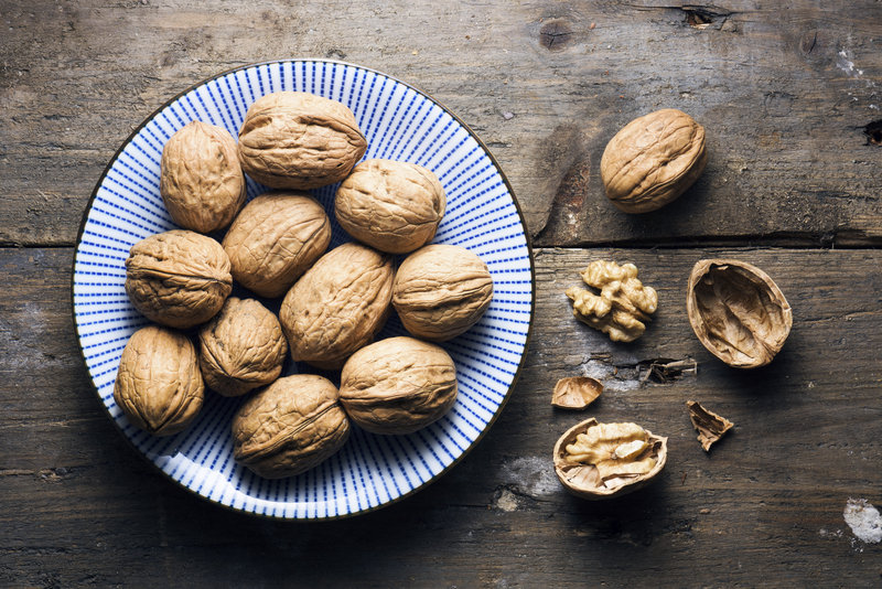 A bowl of walnuts on a wooden table