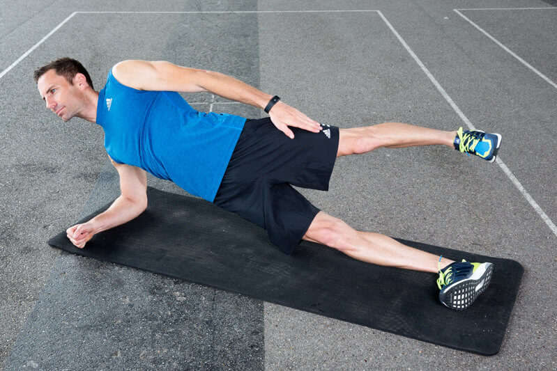 Athletic man makes a low-side plank with foot lift forwards and backwards .