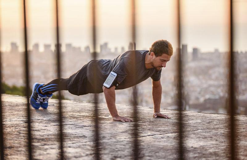 Athletischer Laeufer macht Liegestuetze.