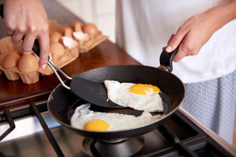 Desayuno proteico: mujer haciendo huevos