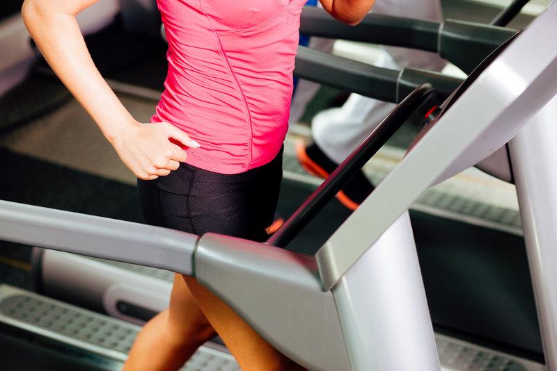 Nahaufnahme von einer sportlichen Frau am Laufband