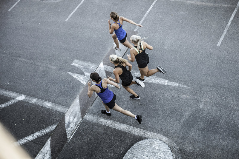 sky shot of four women running together on the street.