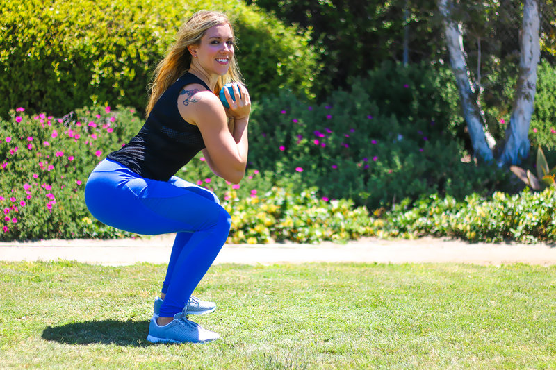 Young woman doing squats with a dumbbell.