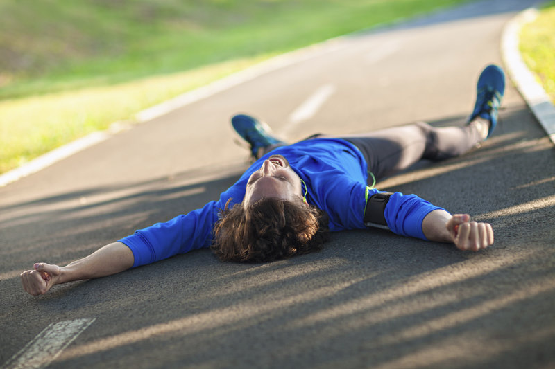 Young man totally exhausted lying on the ground.