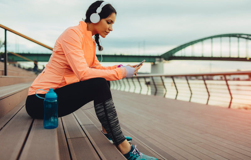 Young woman running in the city. She is sitting and taking break before he continue her daily routine. Sitting on stairs and texting on her smart phone. She is jogging by the river. Listening music with big white headphones.