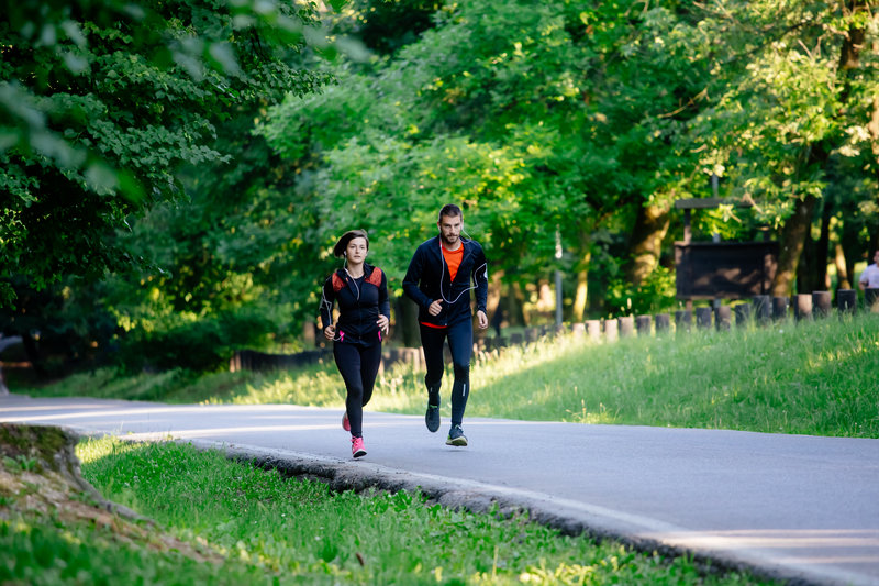 Young couple running together in park