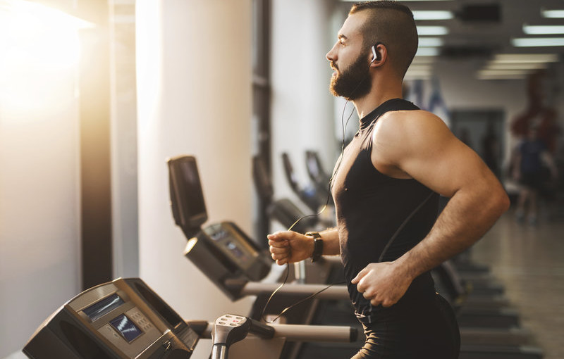 Young muscular man jogging on treadmill in a gym.