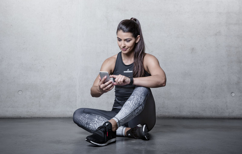 Attractive woman sitting on the floor looking on her phone.