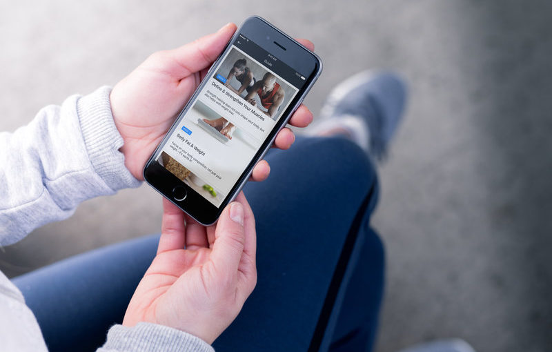 Woman is looking on the screen of her phone.Runtastic Results Health and Nutrition Guide.