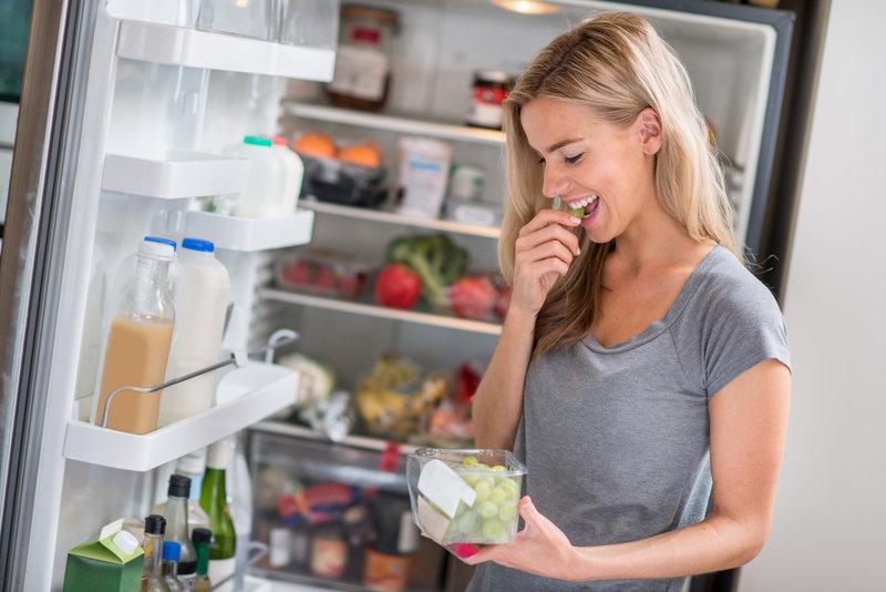 Junge Frau isst Trauben aus dem Kühlschrank