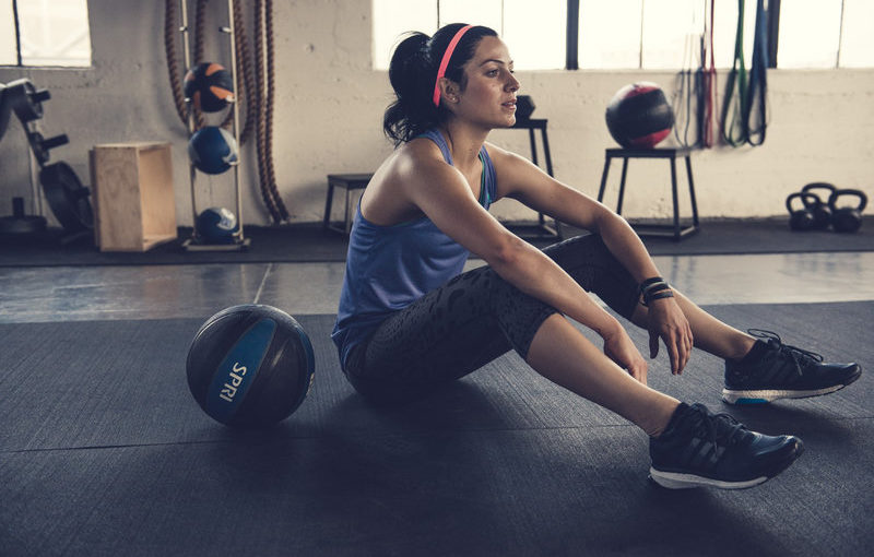 Woman is sitting on the floor after her workout