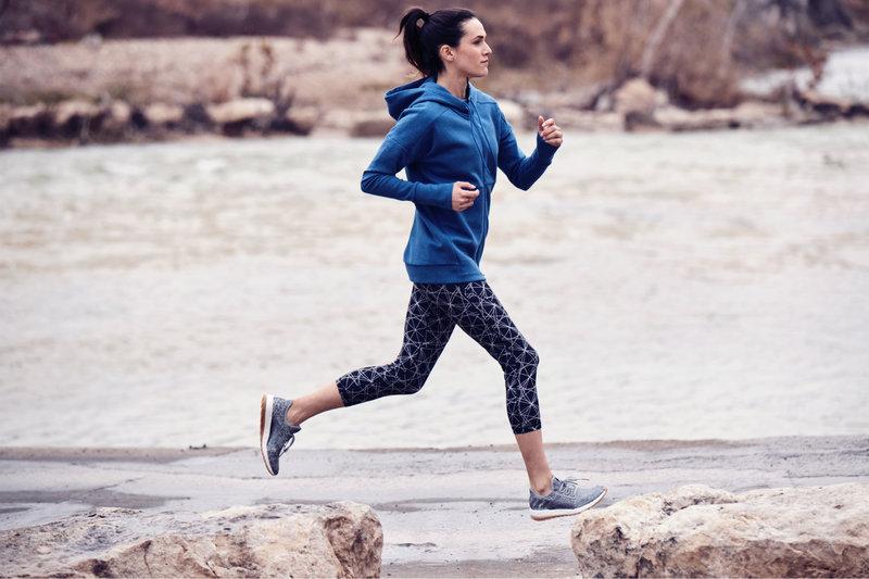 Eine Frau läuft am Fluss entlang