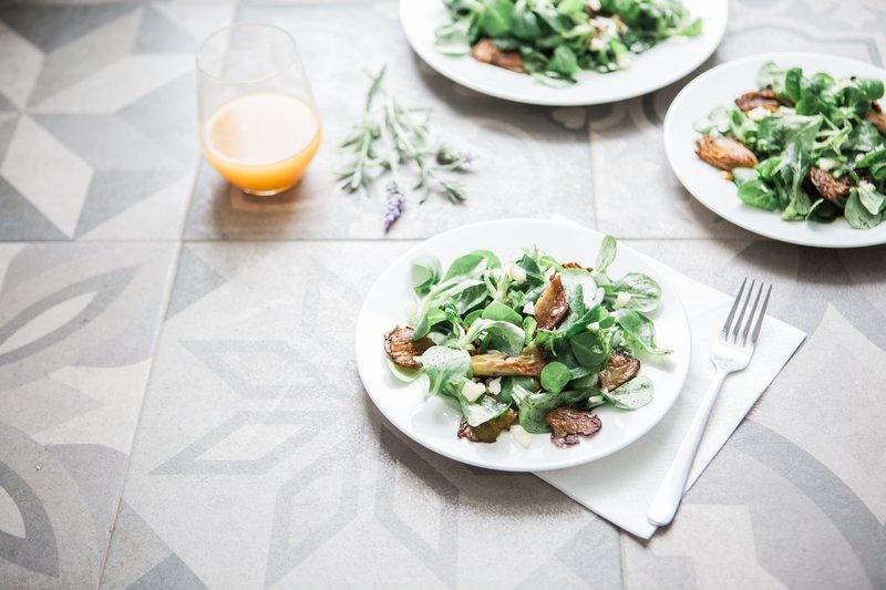 Drei Teller Salat und ein Glas Orangensaft auf einem Tisch