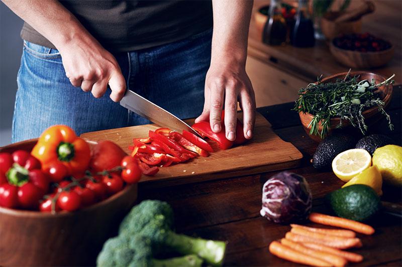 Hombre cortando pimientos