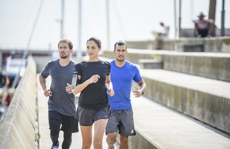 Eine Frau und zwei Männer laufen in der Stadt