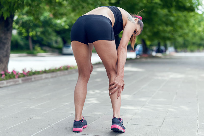 Woman is having a muscle cramp during her run