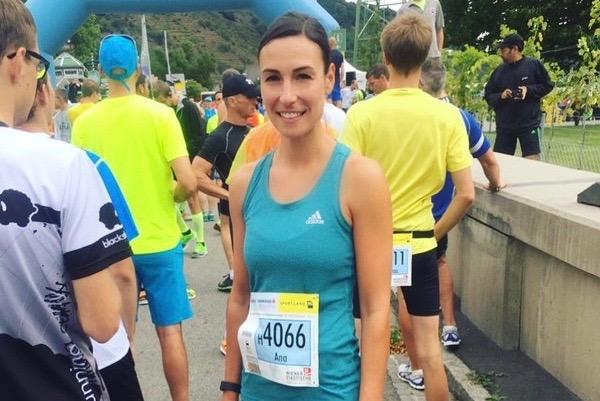 Eine Frau lächelt nach einem Halbmarathon glücklich in die Kamera